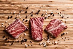 Carne de Kobe sobre tabla de madera con pimienta y sal foto