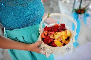 Wedding rose petals at hands of bridesmaids in basket photo