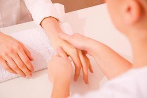 masajista masajeando la mano foto
