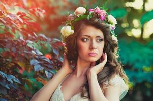 sweet beautiful young woman with a wreath of flowers on photo