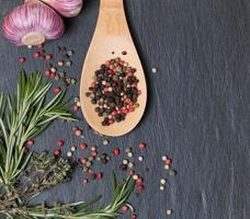 wooden spoon with different pepper, garlic, rosemary and herds