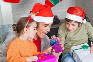 father with two kids open christmas presents