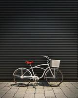 white retro bicycle in front of garage wall photo