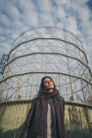 Beautiful young brunette posing in front of a gasometer photo