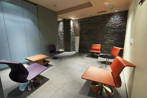 Modern waiting room with stone wall and colorful chairs
