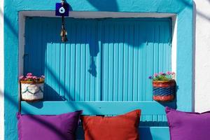 Flowerpots hanged on the  colorful walls and windows in Bozcaada