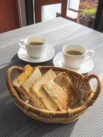Toasts in basket with coffee on table