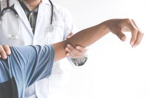 Doctor checking patient' elbow