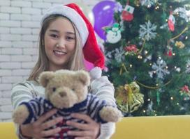 mujer sosteniendo un oso de peluche con un gorro de Papá Noel