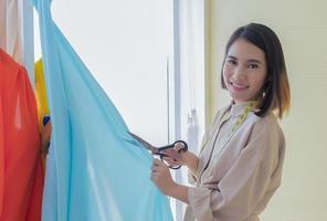 mujer diseñador de moda cortando tela
