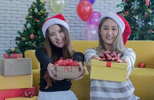 Two women holding out presents