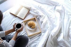 mujer, relajante, cama, con, libro, y, desayuno