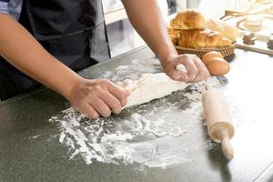Close-up of person kneading dough