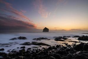 Black rocks on seashore during sunset