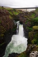 Waterfall under a bridge in Iceland photo