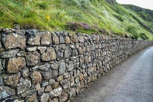 Rock wall along gravel road photo