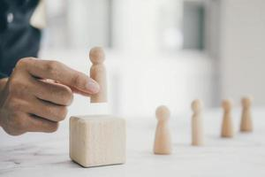 Person placing pawn on wooden block