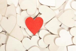 corazón rojo de madera rodeado de corazones blancos