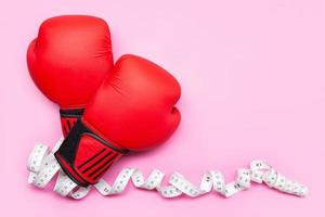 Boxing gloves and measuring tape on pink background photo