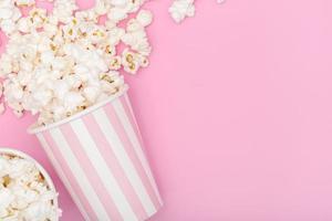 Cubo de palomitas de maíz sobre fondo rosa