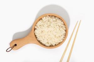 Cooked rice in wooden spoon and chopsticks on white background