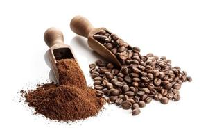 Two wooden scoops with ground and whole bean coffee