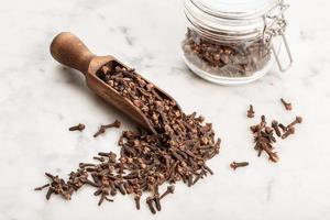 Cloves in a wooden scoop on a marble background