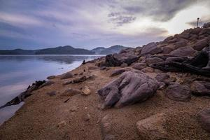 Rocks on a shore with mountains photo