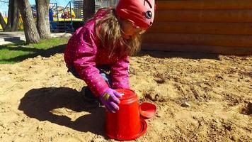 fille enfant jouant dans le bac à sable. fille posant un gâteau sur le sable.
