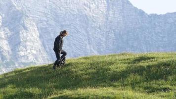 câmera lenta: jovem feliz com seu pequeno cachorro de estimação em uma aventura de caminhada