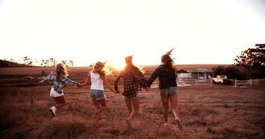 gruppo di amici che corrono durante il tramonto al rallentatore