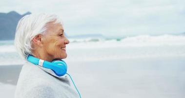 mulher idosa usando fone de ouvido ao redor do pescoço enquanto caminha na praia