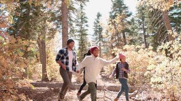 padres enérgicos y dos niños corriendo en el bosque, vista lateral