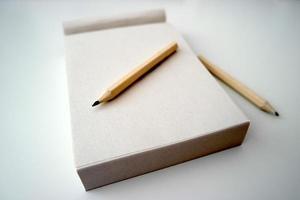 Bloc de notas con lápices sobre una mesa foto