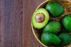 Avocado fruit in a basket on wooden table