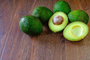 Avocadoes on wooden background