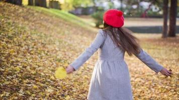 mujer joven, girar, otoño, juego, con, hoja, en el estacionamiento