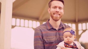 Porträt eines jungen Mannes, der mit seiner kleinen Tochter an einem Herbsttag unter einem Pavillon sitzt