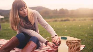 Una mujer joven abriendo una canasta de picnic mientras estaba de picnic con su familia en un día de otoño