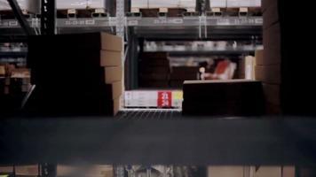 un uomo sta passando per scaffali con merci in scatole di cartone in un magazzino, prendendo una scatola dallo scaffale