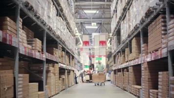 un uomo sta spingendo un carrello pieno di scatole su di esso tra scaffali con scatole di cartone in un magazzino di stoccaggio