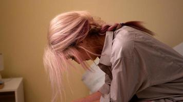 réfléchie jeune blonde assise sur son lit