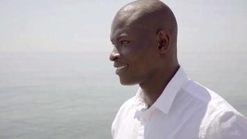 premuroso uomo africano che cammina lungo il mare