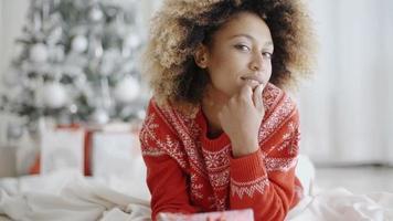 jeune femme réfléchie avec un cadeau de Noël