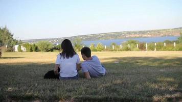 Mann mit dem Mädchen und dem Hund, die am Ufer ruhen
