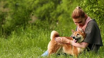 Mädchen umarmt Hund Shiba Inu