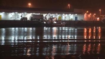 Barcos de pesca descargando pescado de noche. video
