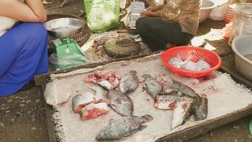 venditore di pesce che compra pesce in una bancarella di pesce al mercato locale