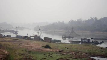 Houseboats and chinese fishing nets in early morning fog