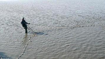 pescador puxando uma rede de arrasto
